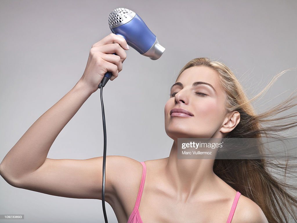 Young woman using hair dryer : Stock Photo