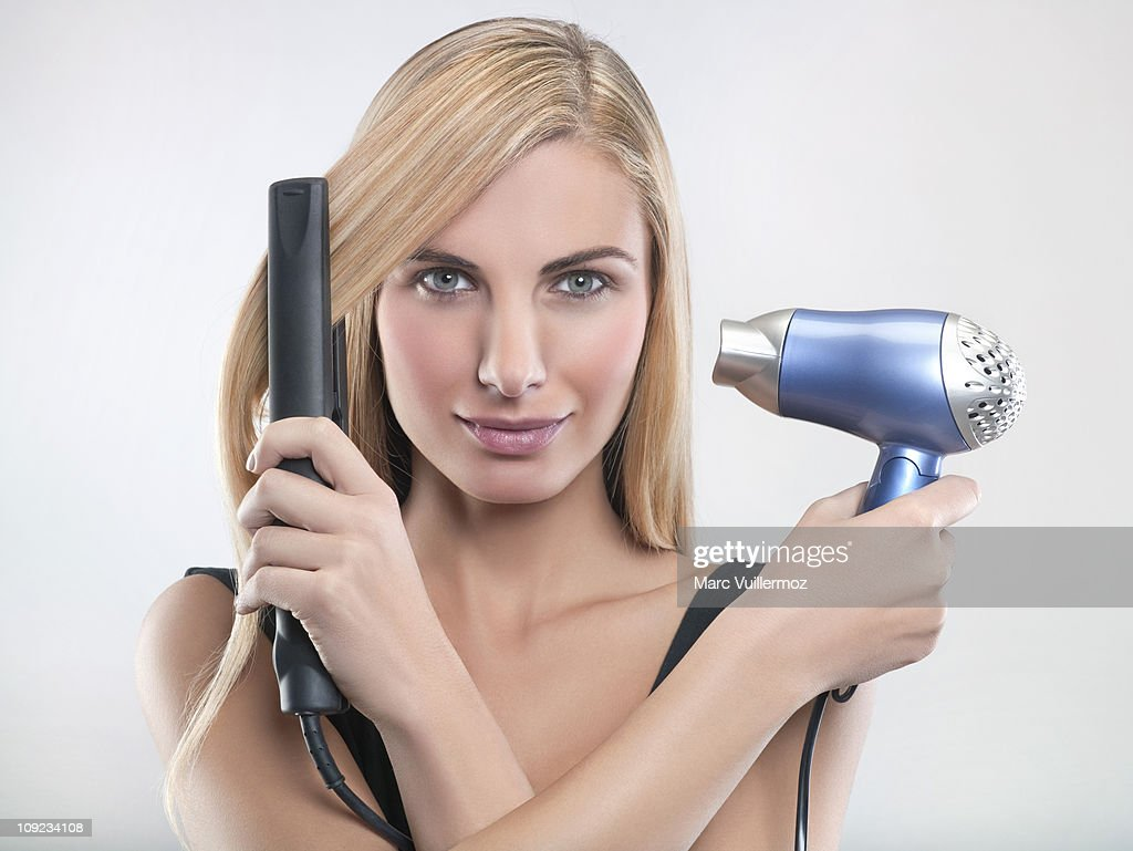Young woman using hair straighteners and hair dryer