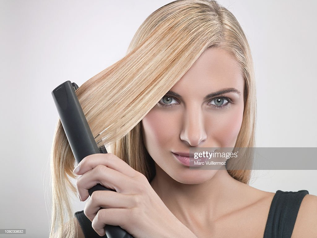 Young woman using hair straighteners