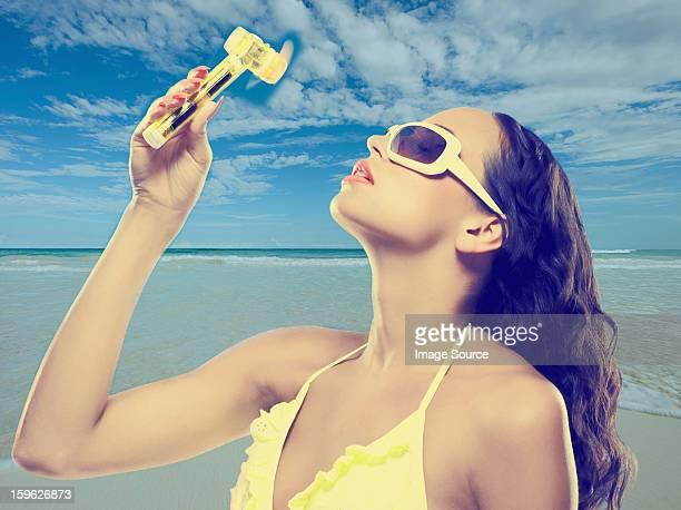 Young woman using hand fan