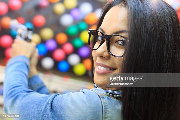 Young woman using handgun for pop a ballon game