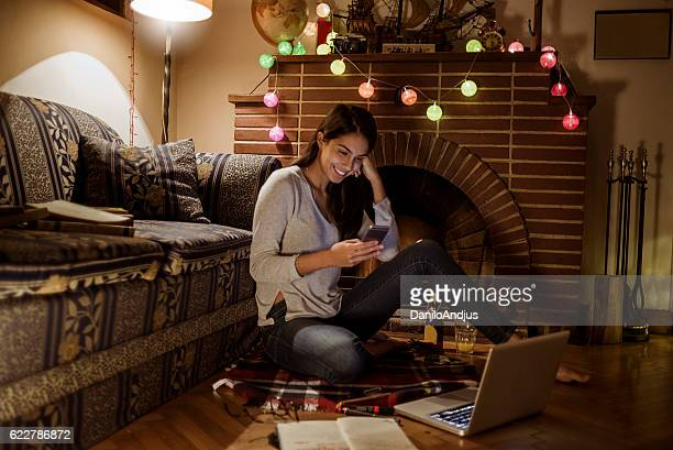 young woman using her smartphone and studying