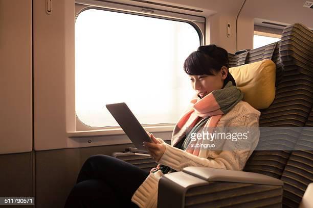 若い女性は彼女のタブレットコンピューターを使用して、列車の旅