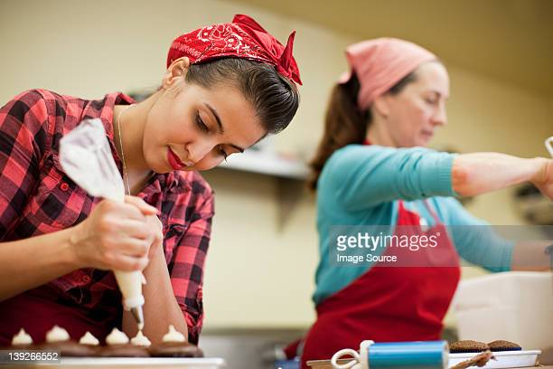 Young woman using icing bag in bakery