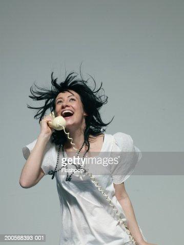 Young woman using landline phone, smiling : Stock Photo