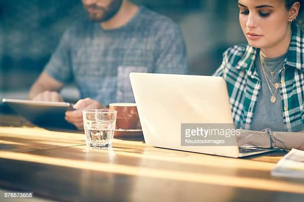 Young woman using laptop by boyfriend inside cafe window