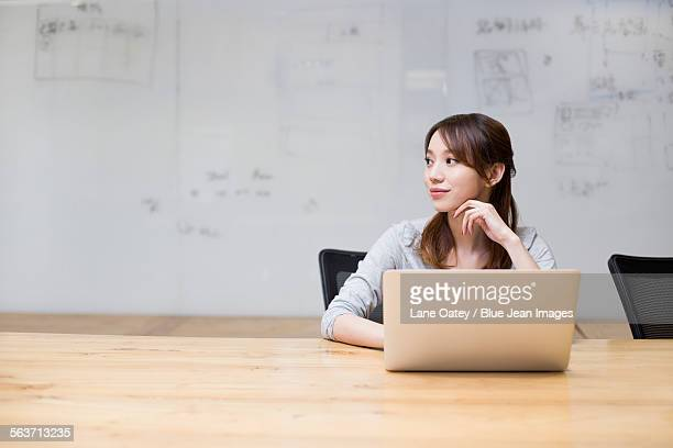 Young woman using laptop in board room