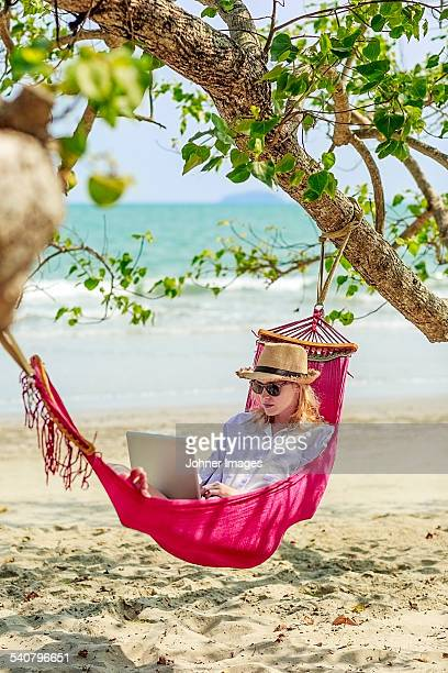 Young woman using laptop in hammock on beach