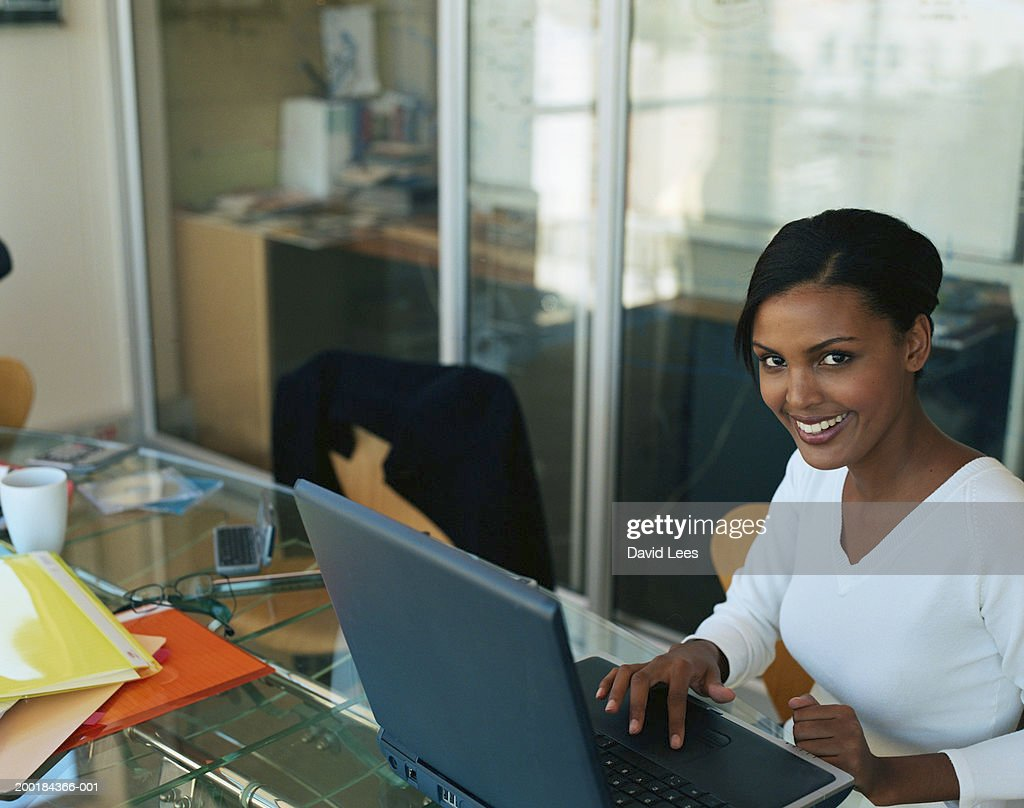 Young woman using laptop in office, smiling, portrait : Stock Photo