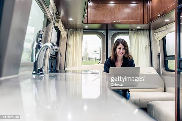Young Woman Using Laptop Inside Motorhome