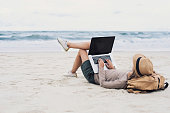 Girl working on laptop computer on a beach. Freelance business concept