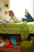 Young woman using laptop on bed in dorm room, side view