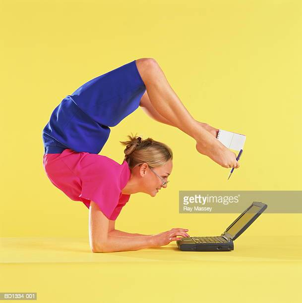 Young woman using laptop on floor, holding notepad and pen with feet