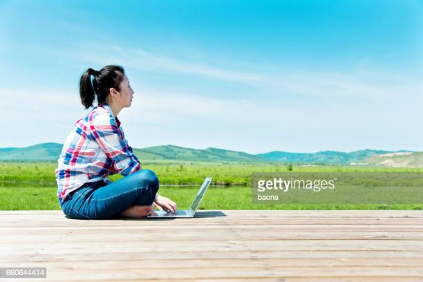 Young woman using laptop outdoors