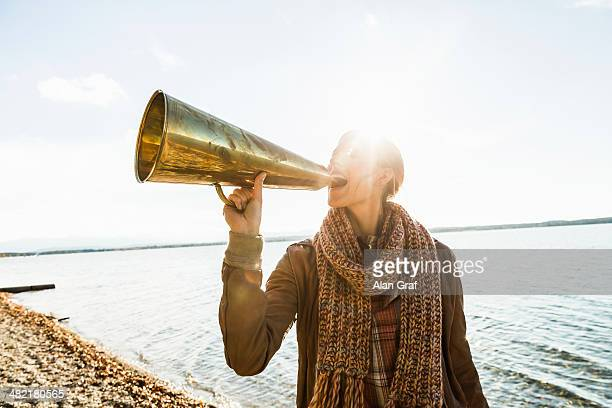 Young woman using megaphone by lake