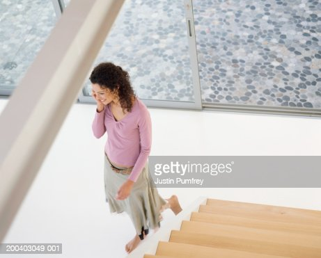 Young woman using mobile at bottom of stairs, smiling, elevated view : Stock Photo