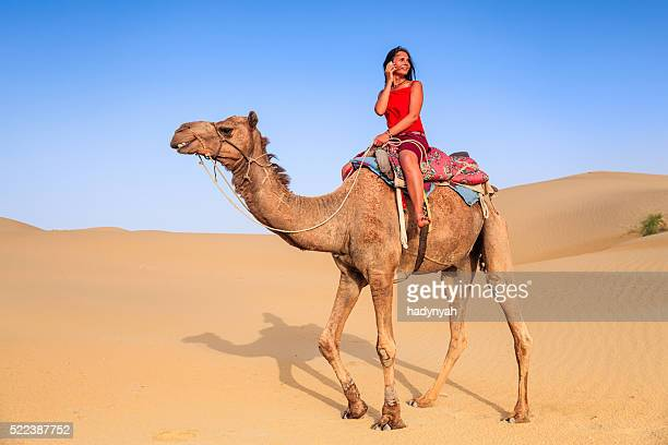 Young woman using mobile on a camel, Rajasthan, India