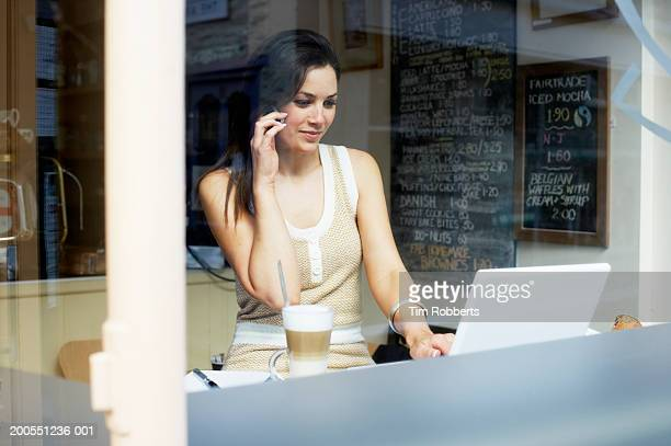 Young woman using mobile phone and laptop in coffee shop
