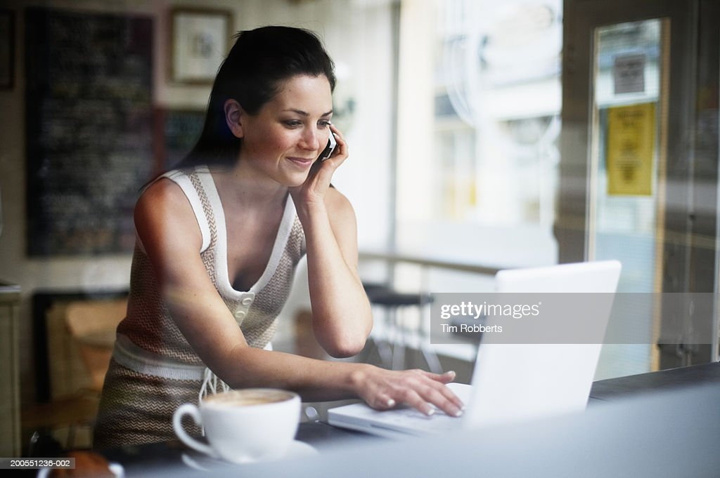 Young woman using mobile phone and laptop in coffee shop, smiling : Stock Photo
