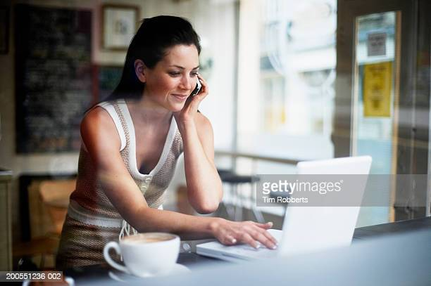 Young woman using mobile phone and laptop in coffee shop, smiling