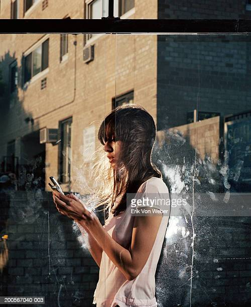 Young woman using mobile phone at city bus stop, side view