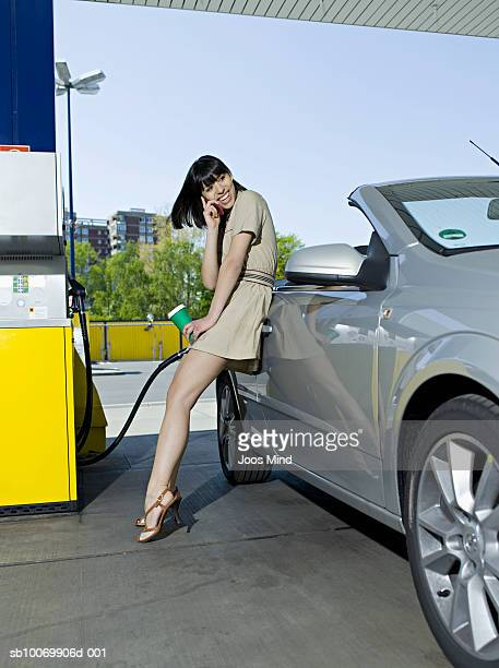 Young woman using mobile phone at petrol station