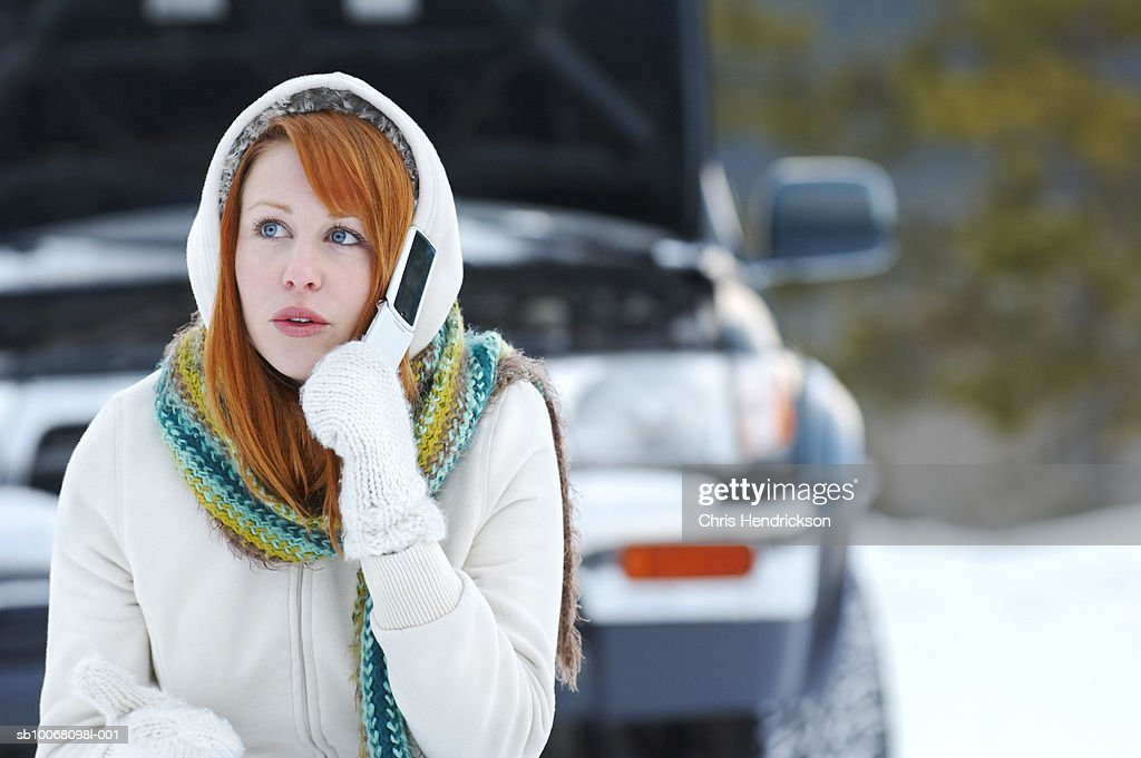 Young woman using mobile phone by broken down car : Stock Photo