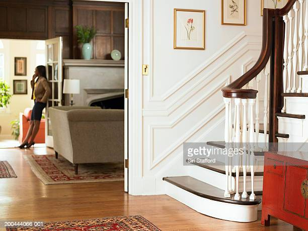 Young woman using mobile phone in living room, entryway in foreground