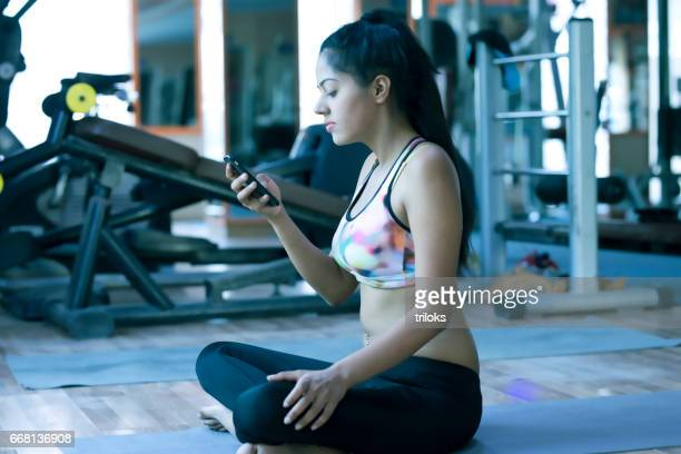 Young woman using mobile phone in yoga class