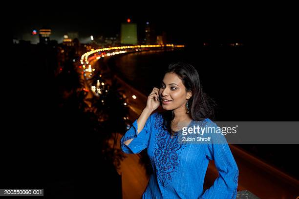 Young woman using mobile phone, night