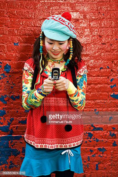 Young woman using mobile phone, smiling, close-up