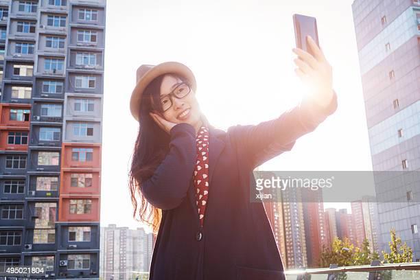 若い女性の携帯電話を使用して自分撮り