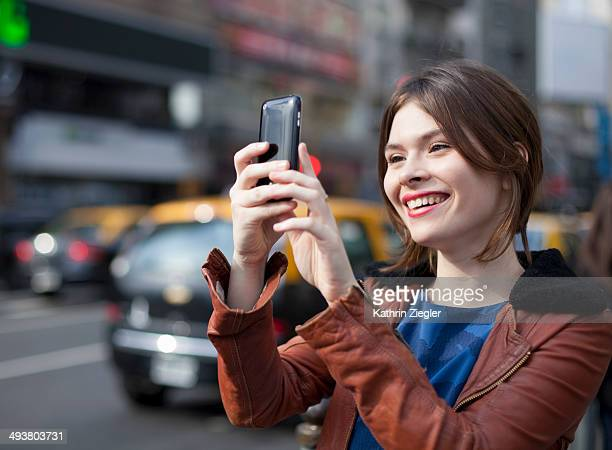 young woman using mobile phone to take a picture
