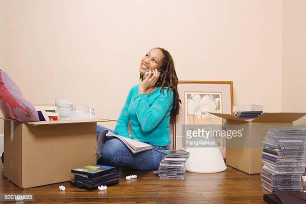 Jovem mulher com telefone móvel enquanto caixas de embalagem