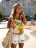 Young woman using mobile phone with handbag, smiling