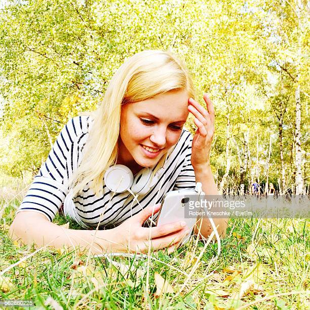 Young Woman Using Mobile While Lying On Grass