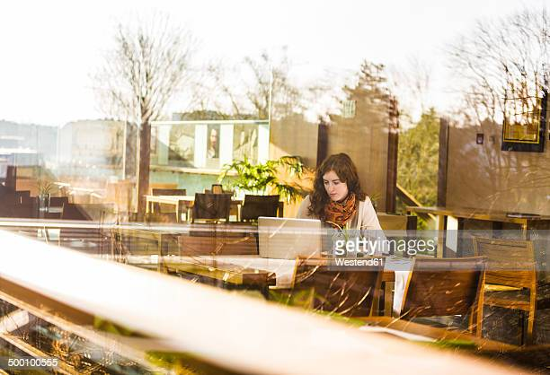 Young woman using notebook in cafe, view from outside