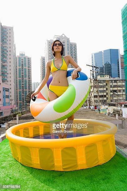 Young Woman Using Paddling Pool on Apartment Block