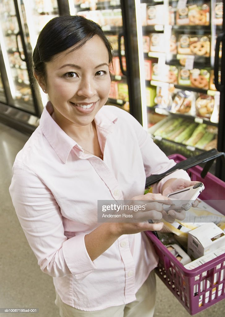 Young woman using PDA phone in supermarket, smiling, portrait : Stock Photo