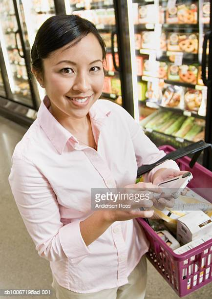 Young woman using PDA phone in supermarket, smiling, portrait