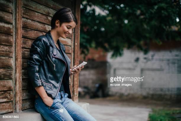 Junge Frau mit Handy gegen die Wand