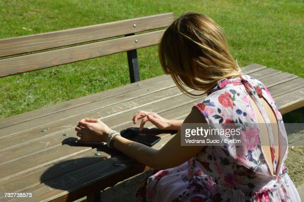 Young Woman Using Phone At Wooden Bench In Park On Sunny Day