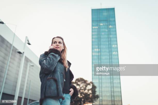Young woman using phone in the city street