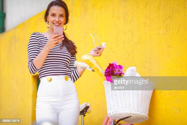 Young woman, using pink smartphone beside the pink bicycle against the yellow wall
