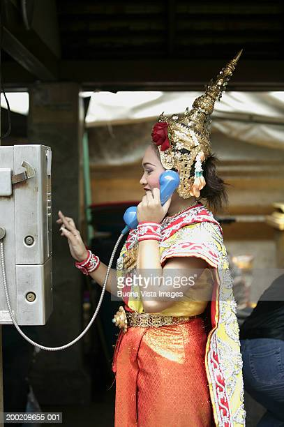 Young woman using public telephone, wearing traditional Thai clothing