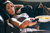 young woman using remote control on sofa
