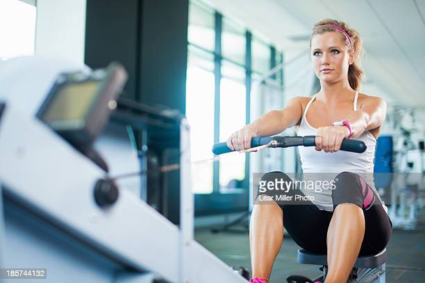 Young woman using rowing machine in gym
