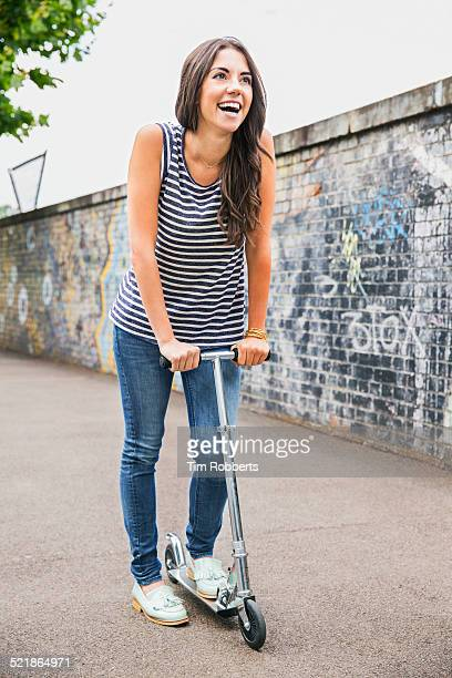 Young woman using scooter.