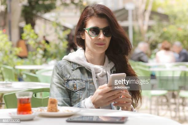 Jeune femme à l'aide de téléphone intelligent à café
