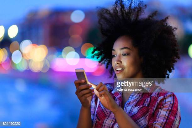 Young woman using smart phone at night on street